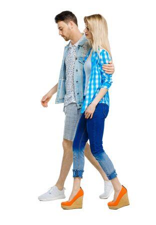Vista lateral de la pareja que va. caminando amigable chica y chico tomados de la mano. Colección de personas de vista trasera. vista trasera de la persona. Aislado sobre fondo blanco.