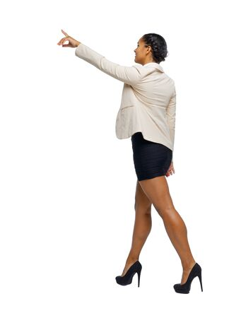 Side view of a black African-American in a suit that goes and points with his hand. backside view of person. Rear view people collection. Isolated over white background. business woman in high heels shoes goes showing hand up.