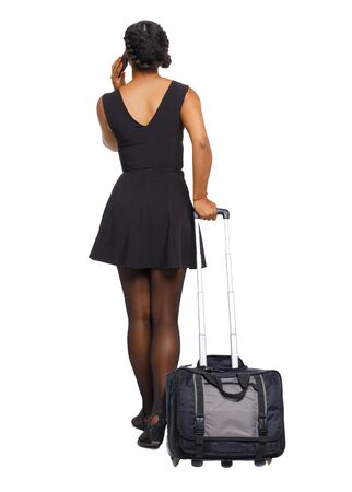 Back view of a black African-American with a suitcase with smartphone. A young traveler calls a taxi at the airport. backside view of person. Rear view people collection. Isolated over white background. Reklamní fotografie