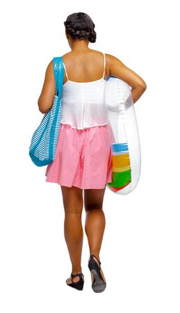 Back view of an African-American with a beach bag that goes to the side. backside view of person. Rear view people collection. Isolated over white background. Black girl carries an inflatable circle to the beach Imagens