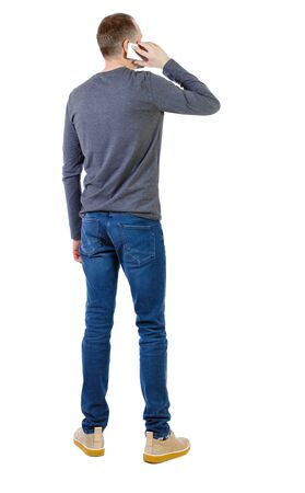 back view of a man talking on the phone. backside view of person. A young guy in a gray jacket talking on a smartphone. Rear view people collection. Isolated over white background.