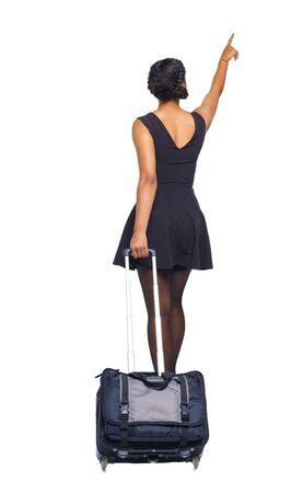 Back view of a black African-American walking with a suitcase and pointing hand forward. Tanned girl in a short dress rolls a suitcase. beautiful girl in motion. backside view of person. Rear view people collection. Isolated over white background.
