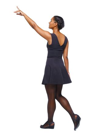 Back view of walking young black girl. going girl showing. backside view of person. Tanned girl in a short dress goes showing a finger to the sky. Rear view people collection. Isolated over white background.