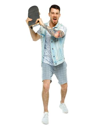 An angry tattooed man attacks. The guy swung to hit the skateboard. Isolated on white background.