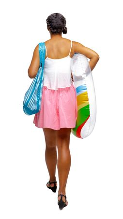 Back view of an African-American with a beach bag that goes to the side. Isolated over white background. Tanned girl with a beach bag and swimming circle goes forward. Imagens