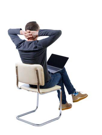 Vista posterior de un hombre que se sienta en una silla con una computadora portátil. Colección de personas de vista trasera. vista trasera de la persona. Aislado sobre fondo blanco. Un hombre con una chaqueta gris se sienta en una silla blanca con una computadora portátil, con las manos detrás de la cabeza. Foto de archivo