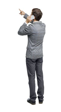 back view of pointing business man in suit talking on mobile phone. rear view people collection. Isolated over white background. backside view of person. Stockfoto