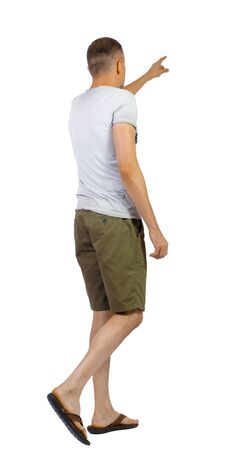 Back view of going pointing man in shorts. walking young guy . Rear view people collection. backside view of person. Isolated over white background.