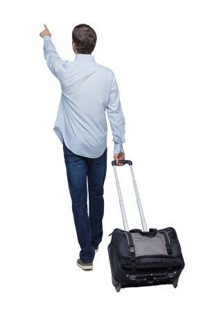 Back view of walking pointing business man with suitcase. gesticulating young guy in suit. Rear view people collection. backside view of person. Isolated over white background.