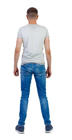 Back view of man in jeans. Standing young guy. Rear view people collection. backside view of person. Isolated over white background. The guy stands with his legs wide apart.