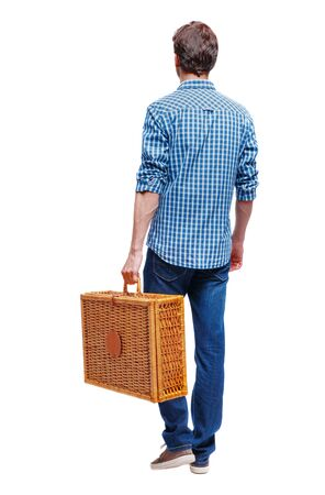 Back view of a man walking with a picnic bag. backside view of person. Rear view people collection. Isolated over white background. A young guy in a shirt goes with a suitcase for picnics.