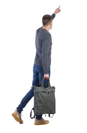 Back view of a walking man with a bag pointing his hand up. backside view of person. Rear view people collection. Isolated over white background. Stylish guy in gray with a big green bag shows his hand up.