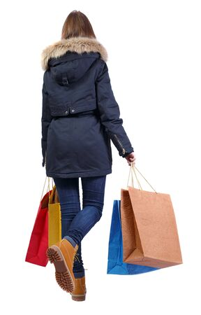Back view of a woman in a winter jacket that comes with paper shopping bags. beautiful girl in motion. backside view of person. Rear view people collection. Isolated over white background. A young girl in a jacket with fur carries shopping bags.