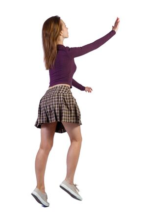 Back view of a woman who comes welcomes someone with hand. backside view of person. Rear view people collection. Isolated over white background. The girl is jumping in a wave of greeting. Stock Photo