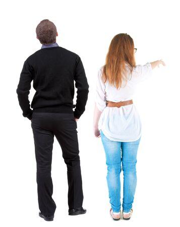 Vista posteriore di una coppia elegante che indica. bella ragazza amichevole e ragazzo insieme. Collezione di persone vista posteriore. vista posteriore della persona. Isolato su sfondo bianco.