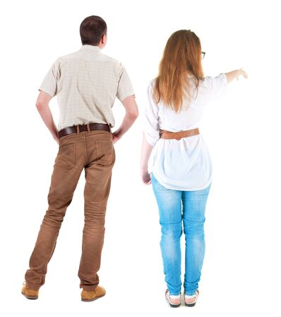 Back view of a stylish couple pointing. beautiful friendly girl and guy together. Rear view people collection. backside view of person. Isolated over white background. Imagens