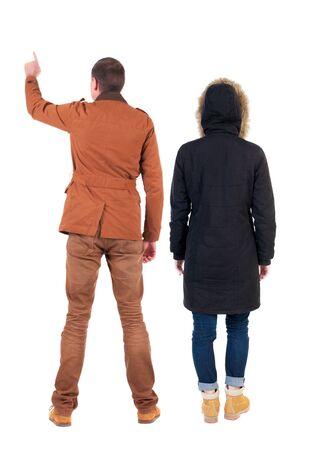 Vista posterior de la pareja pareja en chaquetas de invierno apuntando. hermosa chica amigable y chico juntos. Colección de personas de vista trasera. vista trasera de la persona. Aislado sobre fondo blanco.