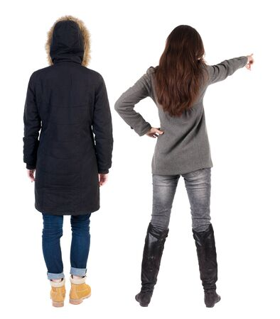 Back view of two pointing young girl in winter jacket. Rear view people collection. backside view of person. beautiful woman friends showing gesture. Rear view. Isolated over white background.