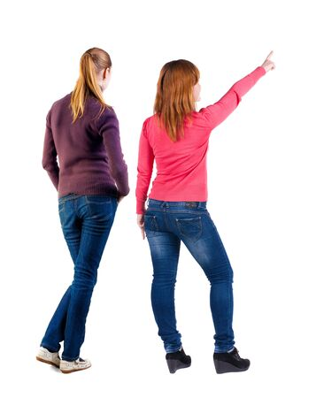 Back view of two pointing young girl in sweater. Rear view people collection. backside view of person. beautiful woman friends showing gesture. Rear view. Isolated over white background.