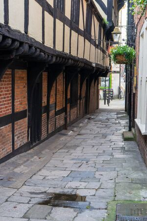 A paved alleyway in an old english town with a tudor building alongside it