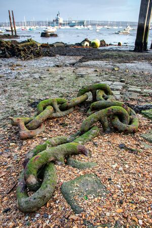 an old iron anchor chain at the seaside at low tide 写真素材