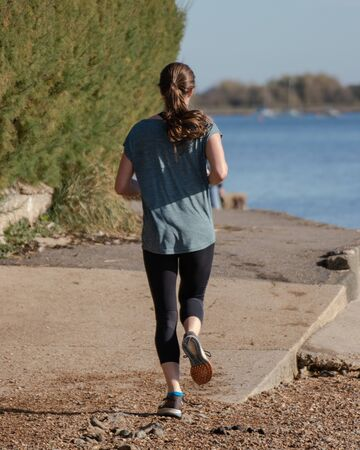 a young girl jogging along the water side or quay