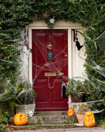 A front door of a house decorated for Halloween with cobwebs and pumpkins Imagens