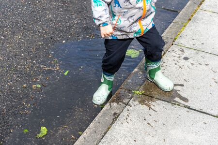a small child wearing wellies or wellington boots splashing in puddles Imagens