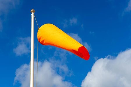 an orange windsock flying in the breeze on a flag pole with a blue sky behind Stock Photo