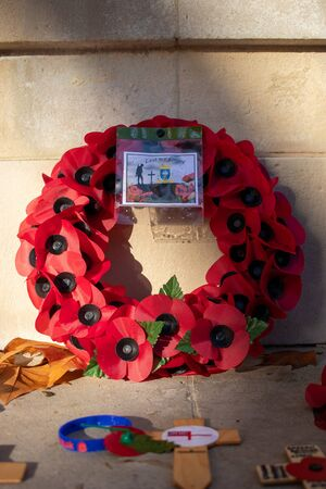 11/11/2019 Portsmouth, Hampshire, UK A red poppy wreath laid in front of a war memorial on remembrance day