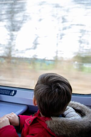 a small boy looking at the window on a moving train