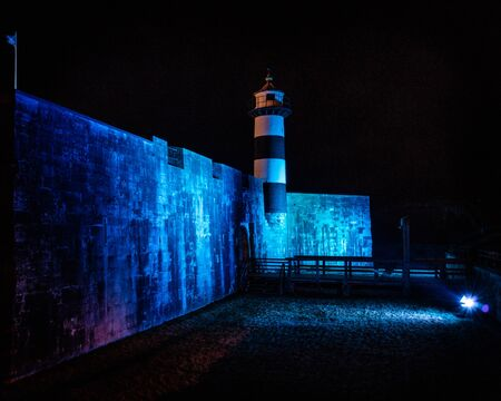 09/14/2019 Portsmouth, Hampshire, UK Southsea castle and lighthouse lit up by blue flood lights at night
