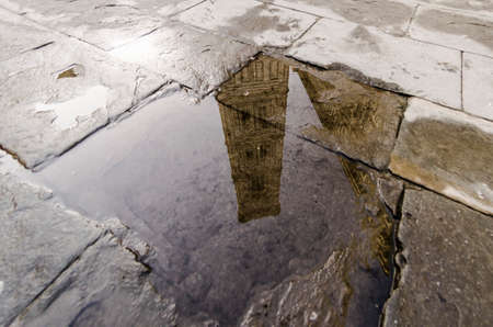 View of Giotto's bell tower in Florence reflected in a puddle
