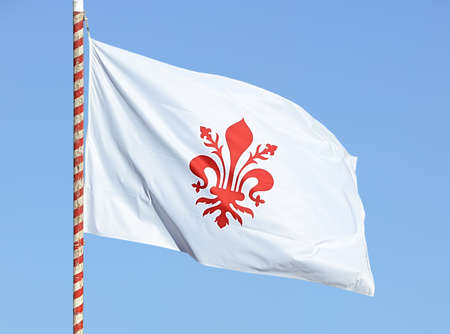 Flag of Florence with red lily waving in the sky 스톡 콘텐츠