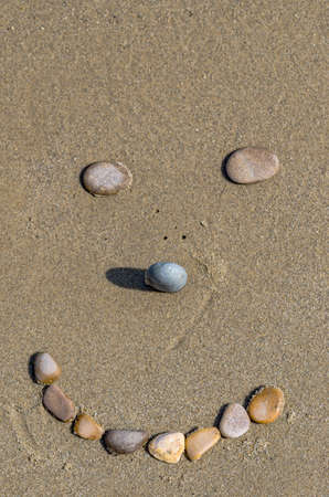 Stones forming a smiling face on the sand