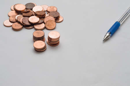 Background with coins and pen on top of a sheet of paper
