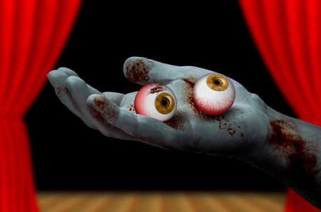Zombie hand holding a pair of eyeballs
