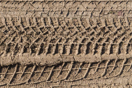 4x4 SUV car leaves a well-formed footprint on the dirty muddy ground after a copious rain photo