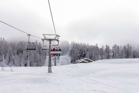 ski runs: Ski lift with passengers in the chair traversing a snow covered mountain slope as it starts the ascent over the evergreen pine plantations to the distant summit and start of the ski runs Stock Photo