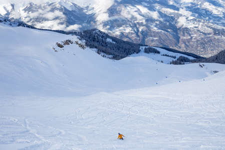 Lone skier in a snowy winter landscape traversing a pristine white valley below rugged mountain peaks photo