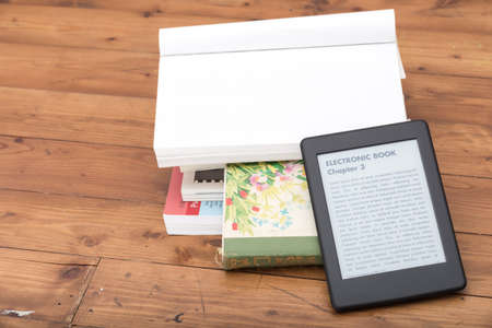 e ink: e-book reader with a nice copy space above done with a white paper of a traditional book Stock Photo