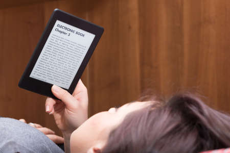 e ink: Brunette GIrl is focused reading an electronic bestseller with her Ebook Reader while she is on the bed