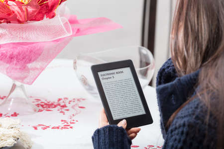 e ink: Lovely close up of e-book reader which is held by a young brunette girl during her reading time