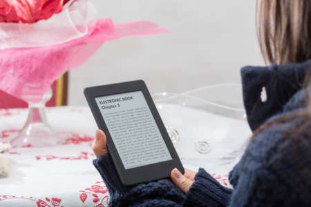 lovely girl: Lovely close up of e-book reader which is held by a young brunette girl during her reading time while is seated in front of a beutiful background of an italian tablecloth.  Stock Photo