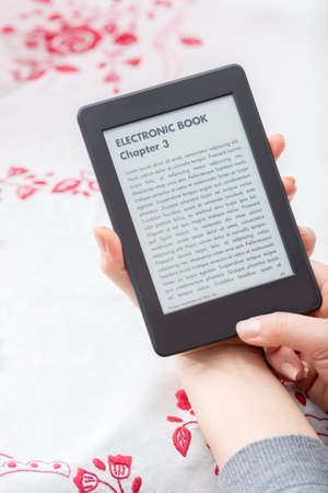 Lovely close up of e-book reader which is held by a young brunette girl during her reading time  photo