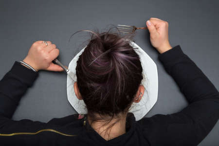 bebes lindos: La muchacha está viendo su plato mientras sostiene a su tenedor y cuchillo. Fondo de pizarra gris.