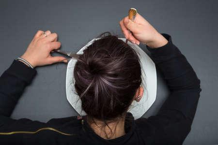 bebes niñas: La muchacha está comiendo su comida de la placa. Ella está poniendo un tenedor en la boca. Fondo de pizarra gris. Foto de archivo