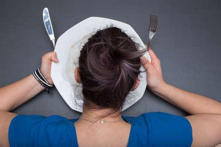 bebes niñas: La muchacha está lamiendo, al igual que un niño, un plato sucio después de que ella ha terminado su comida. Fondo de pizarra gris.
