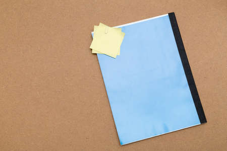 Blue notebook and some notes with free copy space where you can write your message. Everything is placed over a surface of plywood wood photo