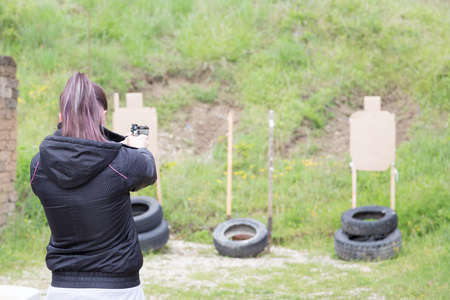 civilian: Civilian girl is practicing with her 9mm gun in a shooting range for improving her self-defense technique with gun